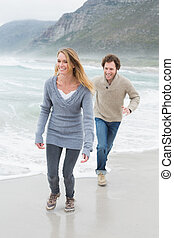 Happy casual young couple running at beach