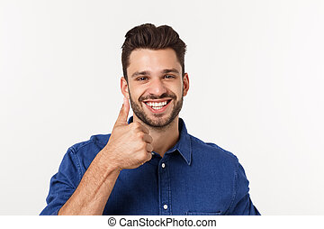 Happy casual young man showing thumb up and smiling isolated on white background.