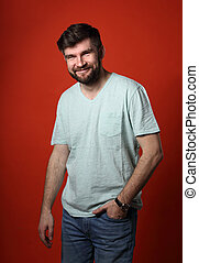 Happy casual young smiling man in t-shirt and blue jeans looking happy on red background. Closeup portrait