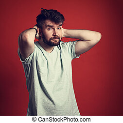 Happy casual young smiling man in t-shirt and blue jeans looking with thinking look on red background. Closeup toned portrait