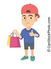 Happy caucasian boy holding shopping bags.