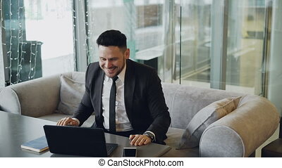 Happy Caucasian businessman in formal wear smiling, raising...