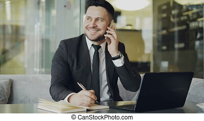 Happy Caucasian businessman sitting, smiling, talking on smartphone with partner and writing down information in notepad while looking at laptop in cafe
