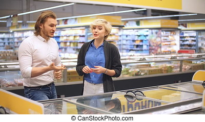 happy caucasian couple choosing frozen food at grocery store in shopping mall.