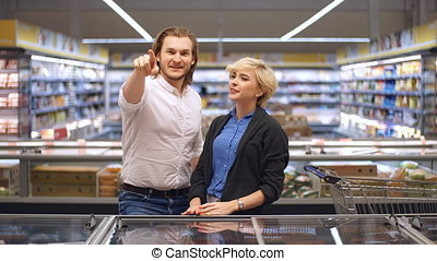 happy caucasian couple choosing frozen food at grocery store...