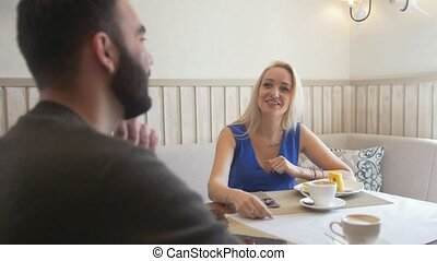 Happy caucasian couple having coffee with desserts on a date at the cafe