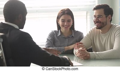 Happy caucasian couple sign mortgage contract handshake african broker