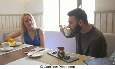 Happy caucasian couple together enjoying a cups of coffee at the cafe