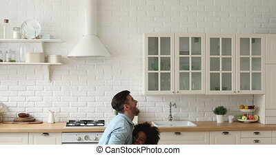 Happy caucasian dad lifting small african daughter playing in kitchen