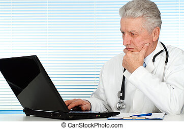 Happy Caucasian doctor with a laptop sitting