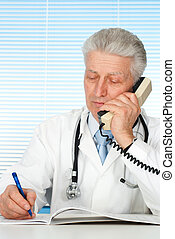 Happy Caucasian doctor with a telephone sitting