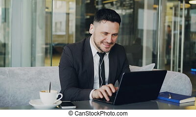 Happy Caucasian entrepreneur in formal clothes typing on his...