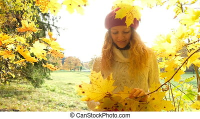 happy Caucasian girl posing with maple leaves in the sun