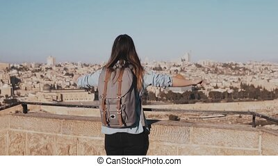 Happy Caucasian girl runs, arms wide open. View of Israel, Jerusalem old town. Excited female tourist. Slow motion.