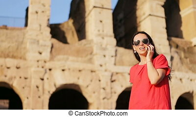 Happy caucasian girl talks by cell phone in front of most popular destination in the world Colosseum in Rome, Italy. Girl enjpy her italian vacation