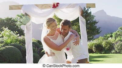 Happy caucasian husband carries newly wed bride and walks down altar outdoors. romantic summer wedding outdoors.