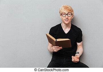 Happy caucasian man reading book.