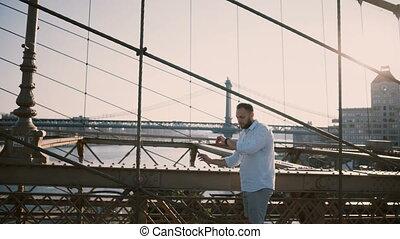 Happy Caucasian man stands alone at Brooklyn Bridge looking...