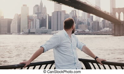 Happy Caucasian man stands near river embankment fence at Brooklyn Bridge scenery, reflecting and enjoying New York view