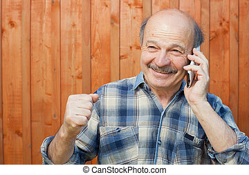 Happy caucasian man with mustache talking on mobile phone.