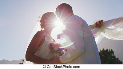 Happy caucasian newly wed couple, standing touching heads at altar outdoors. romantic summer wedding outdoors.