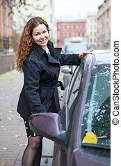 Happy Caucasian woman holding car door handle to sitting in vehicle