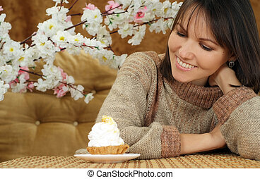 Happy Caucasian woman sitting at a table with a cake on a ...