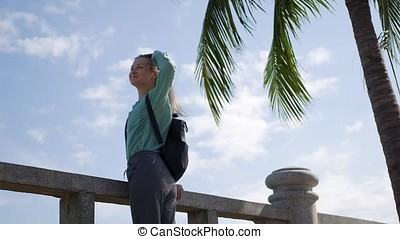 Happy caucasian woman with long blonde hair in sunglasses and green shirt standing and smiling near palm tree on a blue sky background. Travel concept