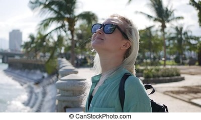 Happy caucasian woman with long blonde hair in sunglasses and green shirt standing and smiling near palm tree on a park and sea background. Travel concept