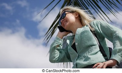 Happy caucasian woman with long blonde hair in sunglasses and green shirt standing and talking on phone near palm tree on a blue sky background. Travel concept