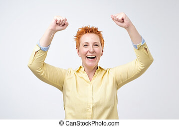 happy caucasian woman with red hair exults pumping fists ecstatic celebrates success