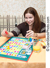 Happy Caucasian young female playing board games in domestic room