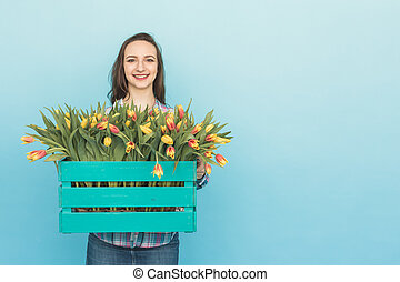 Happy caucasian young woman with box of yellow tulips on blue background