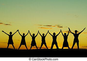 Happy celebrating women at sunset or sunrise standing elated...