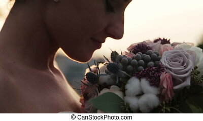 Happy charming brunette bride smiling with bouquet in hands close up