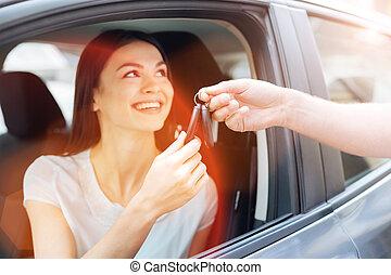Happy charming woman receiving car keys