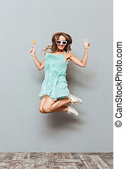Happy charming young woman in sunglasses jumping in the air