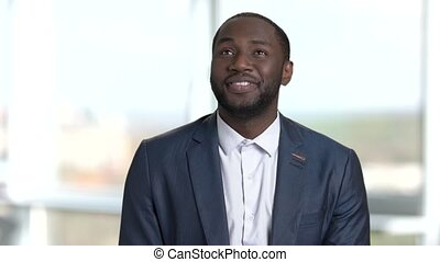 Happy cheerful african man looking around. Blurred windows...