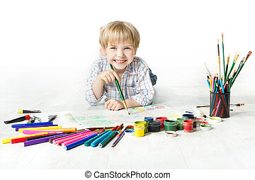 Happy cheerful child drawing with brush in album using a lot...