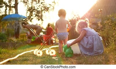 Happy cheerful children playing with water in summer vacation. Cute adorable smiling children spraying with a garden hose in the back yard. Close up