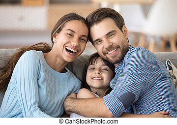 Happy cheerful family embracing sitting on couch at home