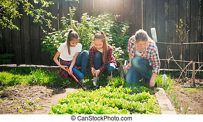 Happy cheerful family working at garden at bright sunny day