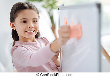 Happy cheerful girl holding a sticky note