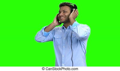 Happy cheerful guy listening to music in headphones.