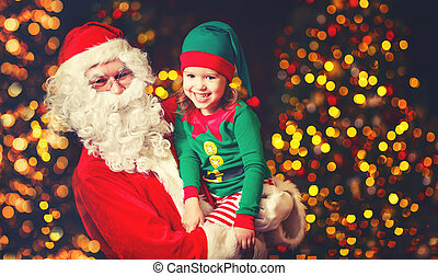 happy cheerful laughing child elf helper and Santa Claus at Christmas