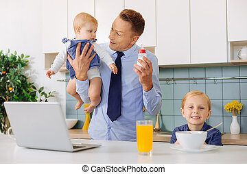 Happy cheerful man having breakfast with his daughters