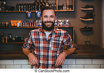 Happy cheerful man with beard in barbershop after visiting barber