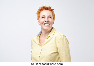 Happy cheerful mature woman with red hair looking at camera with joyful and charming smile.