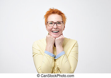 Happy cheerful mature woman with red hair rejoicing at positive news looking at camera with joyful and charming smile.
