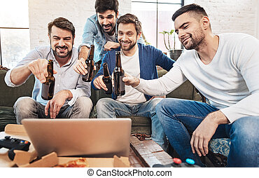 Happy cheerful men drinking beer with their online friends
